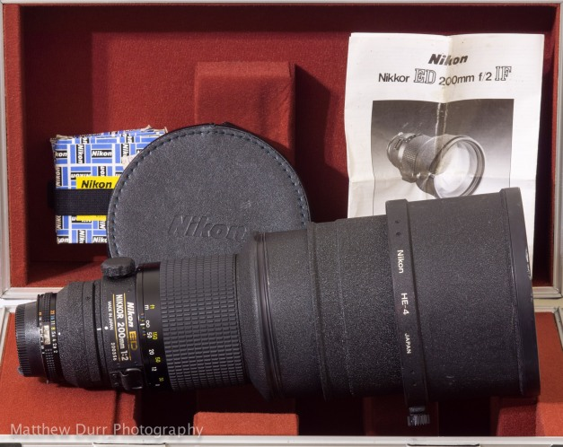 Pictured here with its CT-200 case, the Nikon 200mm often comes with extra gelatin filter holders, a leatherette lens cap, case/lens carrying straps, and instruction manual